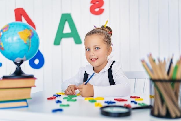 학교로 돌아가다. 책상에서 행복 하 게 웃는 눈동자. 연필, 책 교실에서 아이. 초등학교에서 꼬마 소녀. 가을의 첫날.