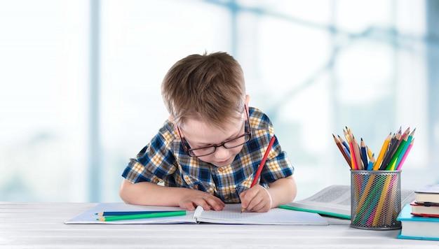 Обратно в школу. счастливый улыбающийся ученик, рисунок за столом.