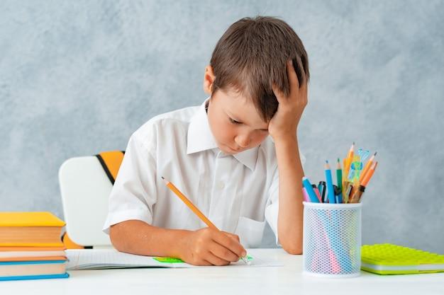 Снова в школу счастливый улыбающийся ученик рисует за партой школьник решает домашнее задание мальчик из эл ...