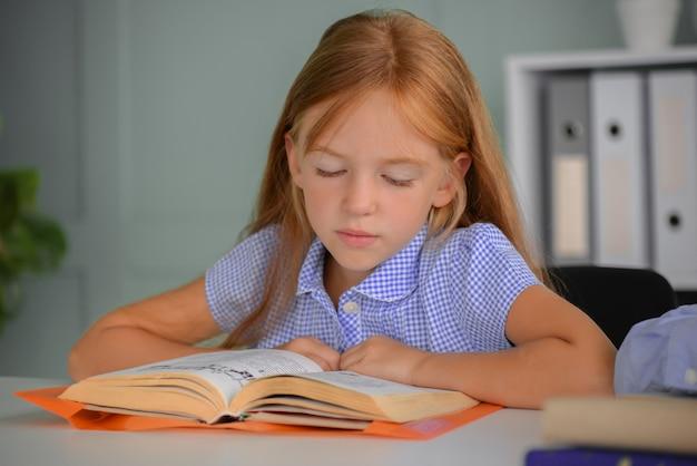 学校に戻る勤勉な子供は屋内のテーブルに座っています女の子は本を読んでいます