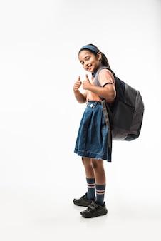 学校に戻る-学校の制服を着たインドの女の子、白い背景の上に孤立して立って出発する準備ができて