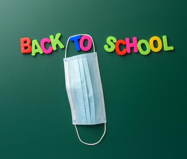 色とりどりのプラスチックの文字と吊りマスクで作られた学校に戻る碑文