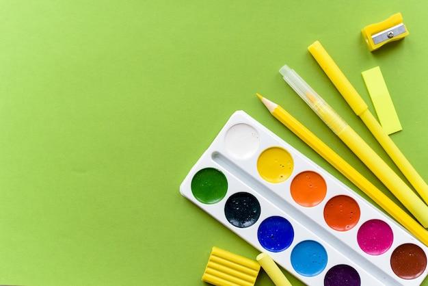 学校に戻る。緑のテーブルの上の学校のためのアイテム。