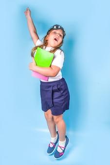 학교로 돌아가기, 과학 교육에서 어린이의 학습 영감, 지식 추구. 흰색 파란색 유니폼을 입은 귀여운 초등학생, 비행 고글, 화려한 파란색 배경에 점프
