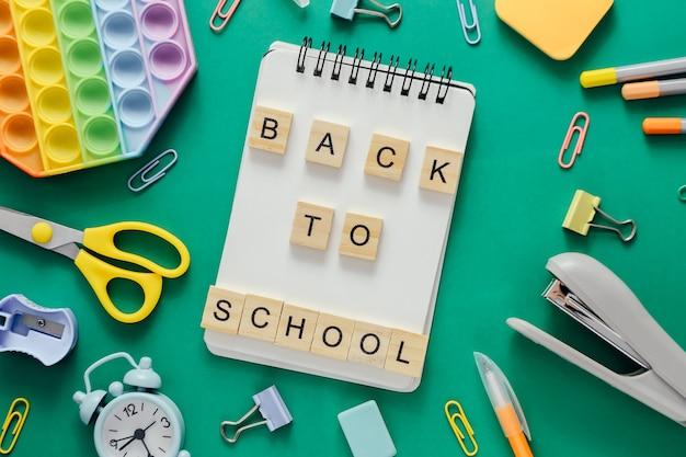 Обратно в школу. макет школьных принадлежностей и канцелярских принадлежностей на фоне зеленой бумаги. студенческая распродажа.