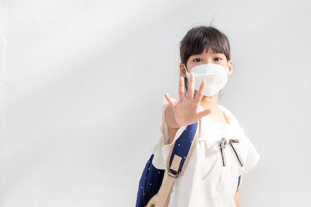 学校に戻る。保護のためにマスクをかぶった小さなアジアの女の子。コロナウイルスの発生を止めるために手を止めるジェスチャーを表示します。