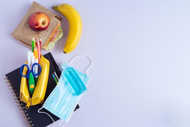 Снова в школу. карандаши, блокнот и бутерброд на фиолетовом фоне. скопируйте пространство.