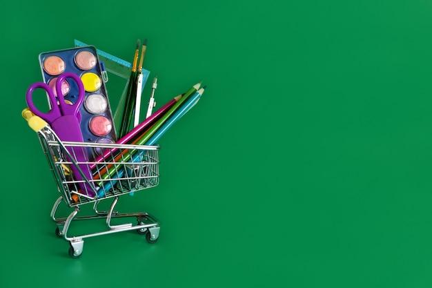 Обратно в школу. мини-корзина с карандашами и школьными принадлежностями на зеленом фоне. школьный баннер