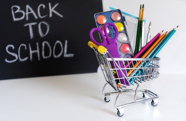 Обратно в школу. мини-корзина с карандашами и школьными принадлежностями на белом фоне. школьный баннер