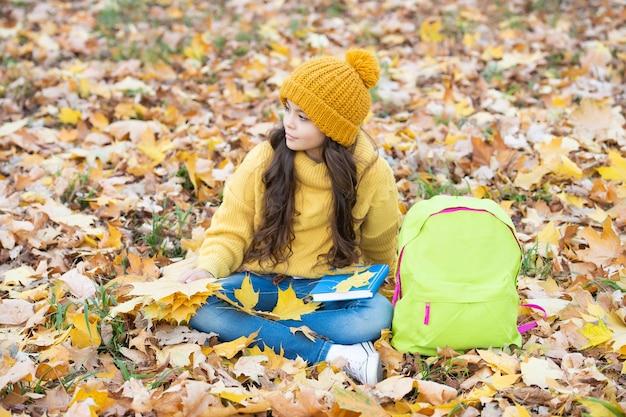 学校に戻る。自然の美。秋のファッション。帽子をかぶった十代の少女は秋の葉を保持します。子供は屋外で黄色のカエデの葉とバックパックでリラックスします。秋の自然。