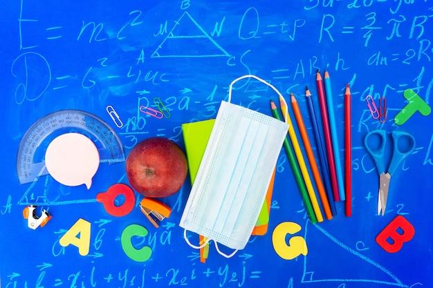 Снова в школу, новая нормальная концепция со школьными принадлежностями на классическом синем фоне с математическими формулами