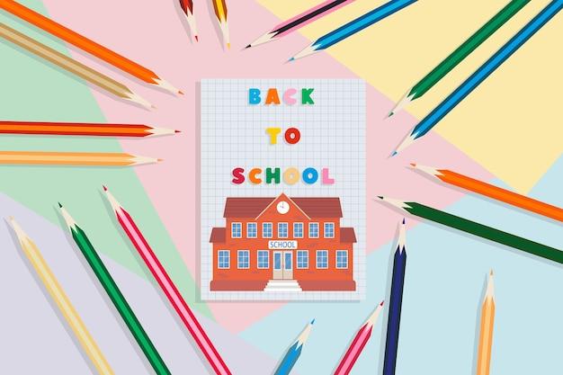 学校に戻る色とりどりの背景にノートの鉛筆と校舎教育