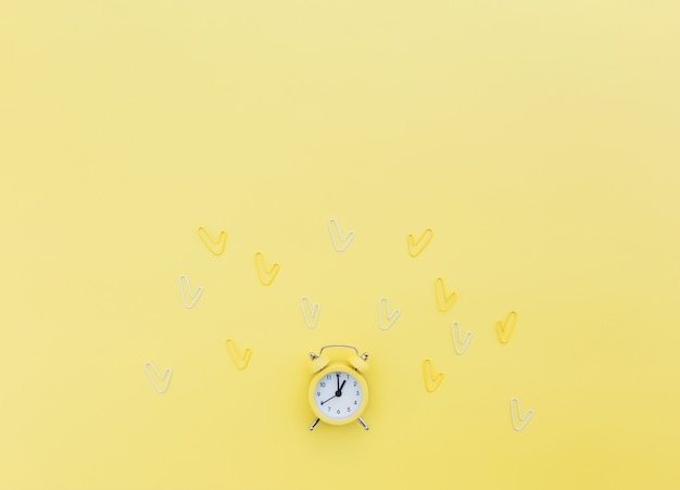 학교로 돌아가서 사무실 작업 개념적 평면에는 알람 시계, 클립 및 텍스트 복사 공간 영역이 있습니다. 일할 시간의 개념, 정시에 있고 일찍 일어나는 아이디어. 노란색 배경과 알람시계
