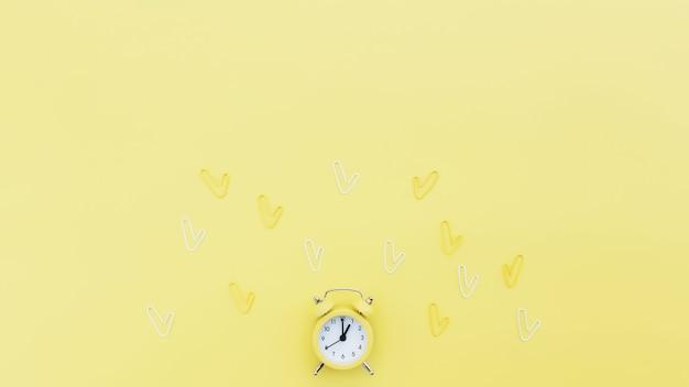 学校に戻ると、目覚まし時計、クリップ、テキスト用のコピースペース領域を備えた事務作業の概念的なフラットレイ。働く時間の概念、時間内にあり、早起きのアイデア。黄色の背景と目覚まし時計