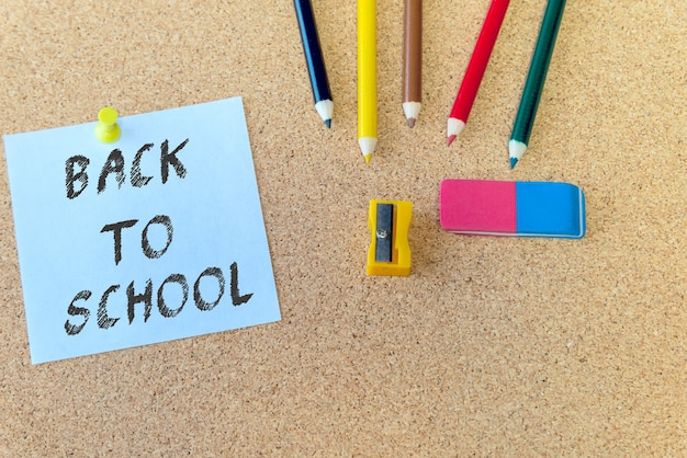 Обратно в школу на синей записке с цветными карандашами на фоне пробковой доски с копией пространства