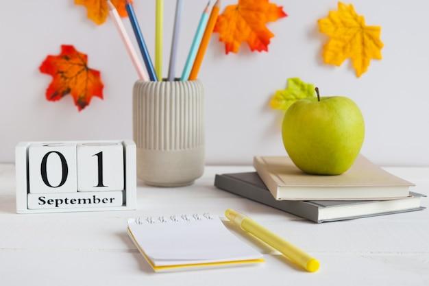 Снова в школу открытый блокнот с ручками, блокноты, карандаши, яблоко и календарь, датированный 1 сентября