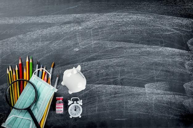 学校や大学のコンセプトに戻る学用品の文房具とサージカルフェイスマスクの上面図