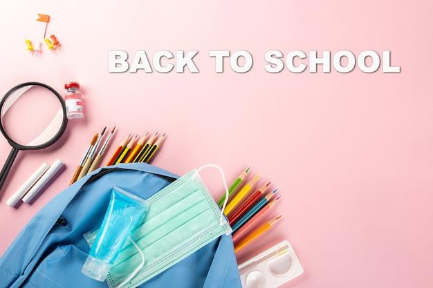 学校や大学に戻る学用品のトップビュー文房具のバックパックとサージカルフェイスマスク