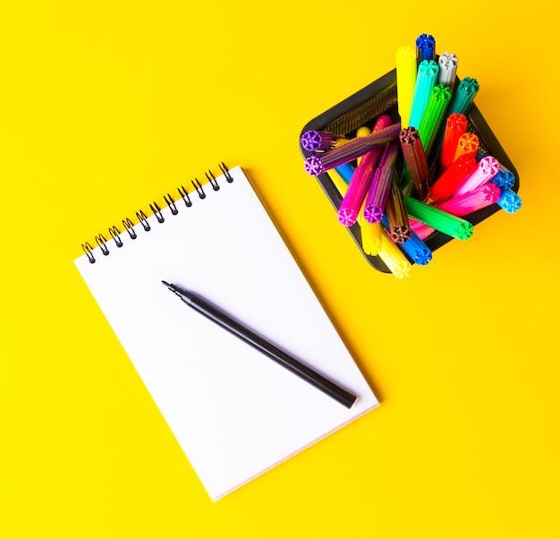 学校や事務用品に戻って、黄色の学用品、学校の概念的な背景に戻る。テキストのための場所、トップビュー。