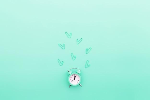 学校や事務作業に戻る目覚まし時計とクリップを備えた概念的なフラットレイ