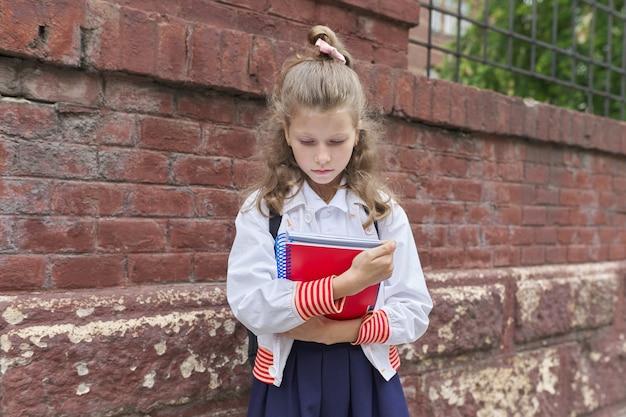 学校に戻る。フェンス校舎のレンガの壁の近くの美しいブロンドの女の子の屋外の肖像画