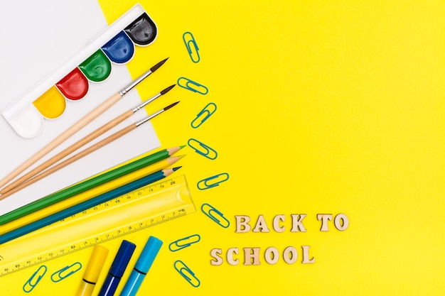 Обратно в школу. принадлежности для рисования и надпись деревянными буквами на желтом фоне. вид сверху