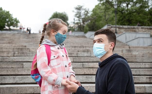 Снова в школу, пандемия. молодой отец и маленькая дочь в маске.