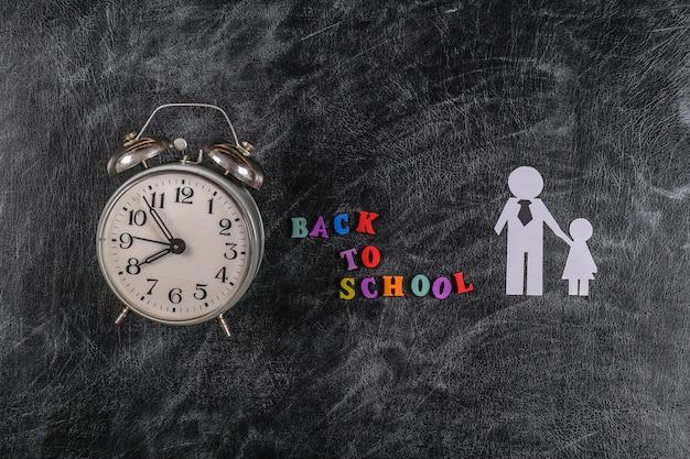 학교로 돌아가다. 학교와 알람 시계로 문자가 있는 분필 칠판에 딸이 있는 종이 아버지