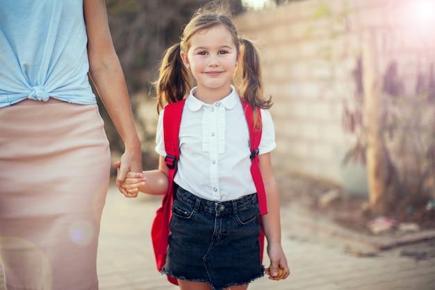 Обратно в школу. концепция родительского ухода. ученица и мама ходят в школу.