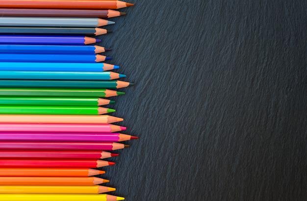 学校に戻る鉛筆は、黒い板の背景に虹の境界線を着色します