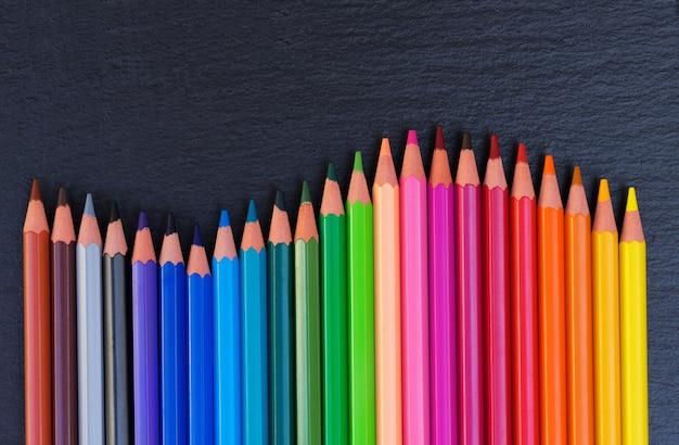 学校に戻る鉛筆黒の背景に虹の境界線