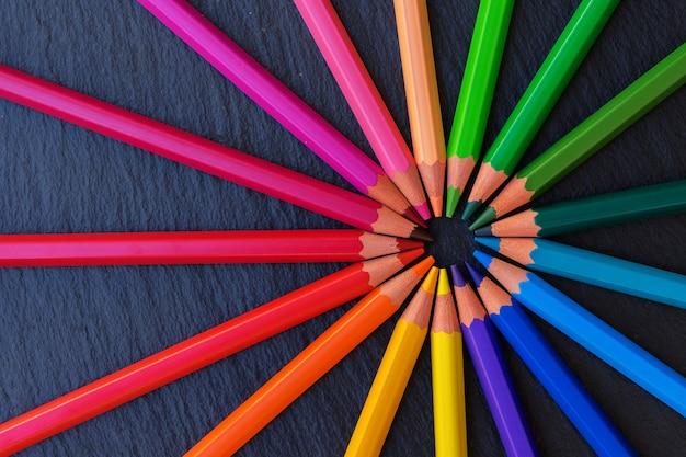 学校に戻る黒の背景に虹の鉛筆