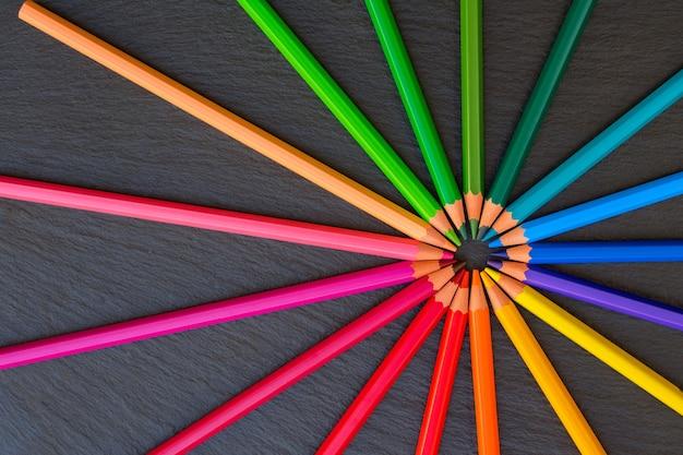 黒の背景に学校の鉛筆の虹のパターンに戻る