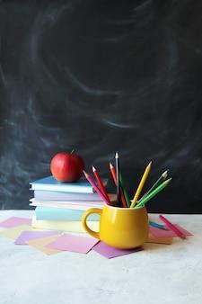 학교 연필로 돌아가서 칠판 개념의 배경에 책과 종이 더미