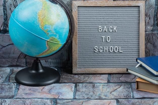 地球儀が周りにある灰色の組織に埋め込まれた学校に戻るフレーズ
