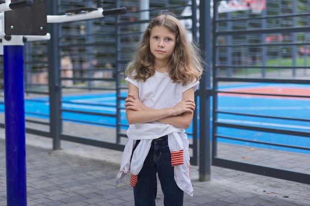 学校に戻る、学校のバスケットボールコートの近くの8、9歳の自信のある女児の肖像画。研究、スポーツ、新しい知識とスキルの始まり