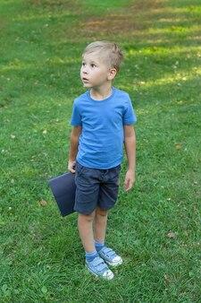Обратно в школу. портрет счастливого улыбающегося ребенка мальчика с книгами в руках в парке.