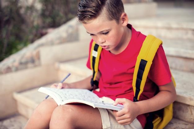 Обратно в школу. открытый ученик читает книгу. концепция детства и знаний