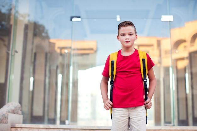 Обратно в школу. ученик с рюкзаком готов к школе, оставаясь на открытом воздухе