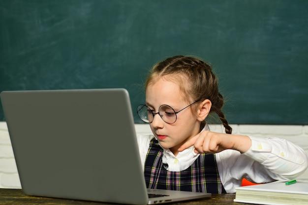 학교로 돌아가다. 노트북 컴퓨터에서 작업하는 학생