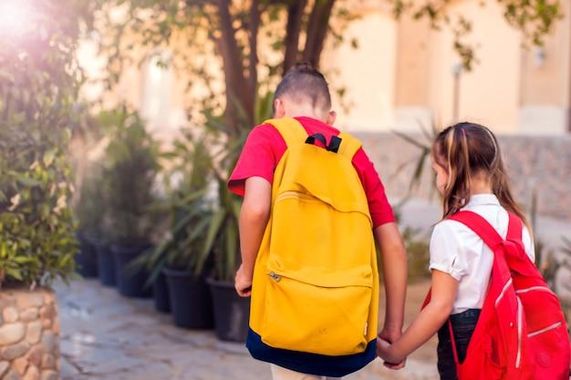 学校に戻る。学校に行くバックパックを持つ生徒