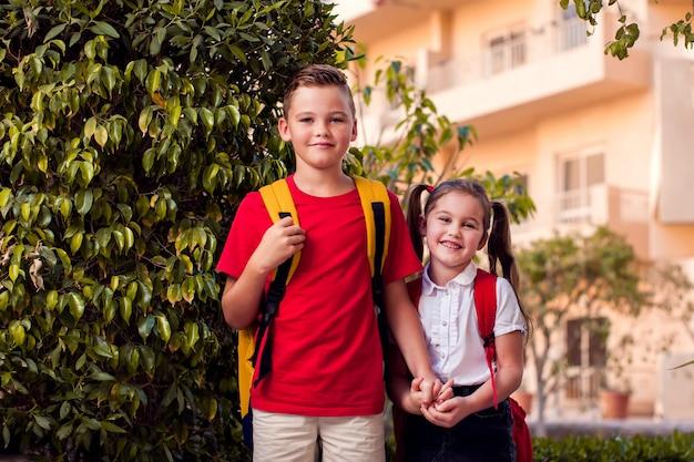 学校に戻る。学校に行く準備ができている屋外のバックパックと生徒