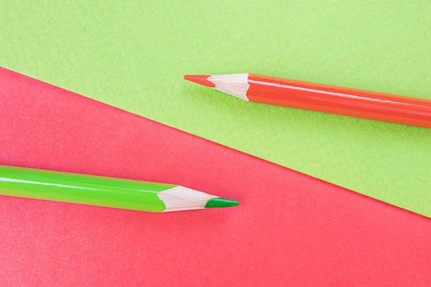 Обратно в школу. красный и зеленый карандаши лежат на пространстве одного цвета. креативная минималистичная концепция детского творчества, рисования.