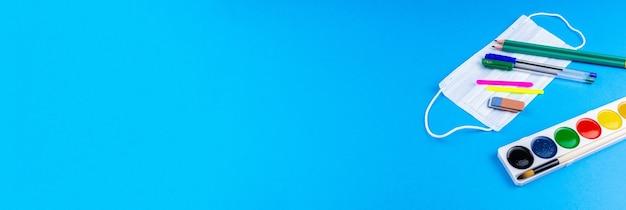 学校に戻る。青い背景の学校のアクセサリー。写真バナー、上面図、テキスト用のスペース。