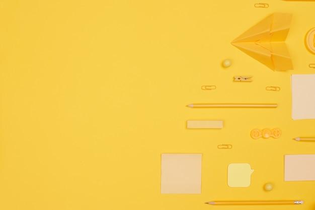 Обратно в школу, школьные принадлежности, лежащие параллельно на желтом фоне, копировальное пространство, вид сверху