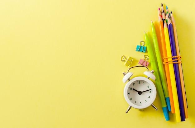 学校に戻る。黄色い紙の背景に学用品。コピースペース