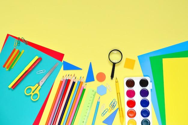 Обратно в школу. школьные принадлежности на желтом столе.