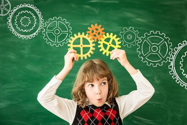 学校に戻るクラスの小学生緑の黒板に対する幸せな子供教育と創造性