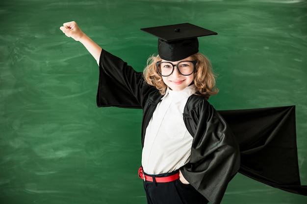 Снова в школу школьник в классе счастливый ребенок против зеленой доски образование и творчество