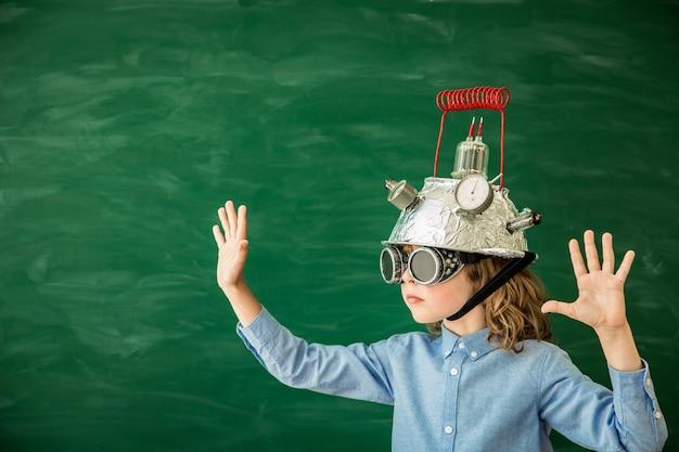 Снова в школу школьник с гарнитурой виртуальной реальности в классе на фоне зеленой доски